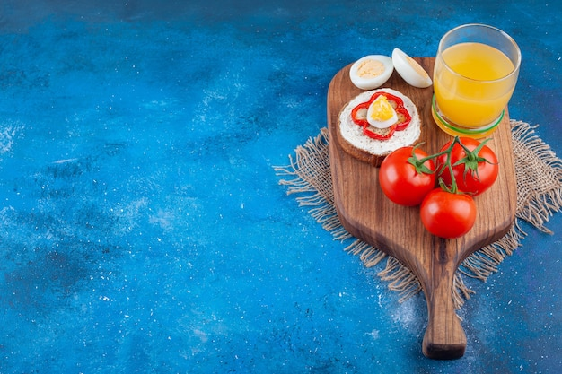 Una tazza di vetro di succo con panino e due pomodori rossi su un pezzo di legno.