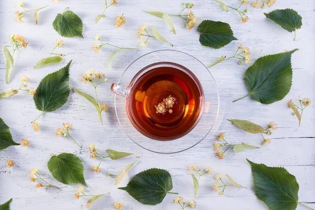Tazza di vetro di tè di tiglio e fiori di tiglio su una vista dall'alto di un tavolo in legno bianco. bevanda calda sanitaria.