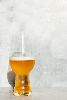 Bicchiere di vetro servito con birra ipa e una bottiglia e una lattina sul fondo