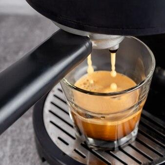 Tazza di vetro in piedi sulla grata della macchina per caffè nero e caffè che vi versa dentro. processo di preparazione del caffè.