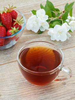 Vetro tazza di tè, ciotola con fragole fresche e fiori di gelsomino bianco su fondo di legno. vista dall'alto.