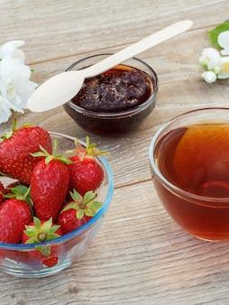 Vetro tazza di tè, marmellata di fragole fatta in casa e fragole fresche in ciotole e fiori di gelsomino bianco su fondo di legno. vista dall'alto.