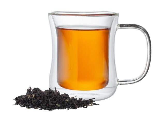 Tazza di vetro di tè con foglie di tè secche isolato su sfondo bianco