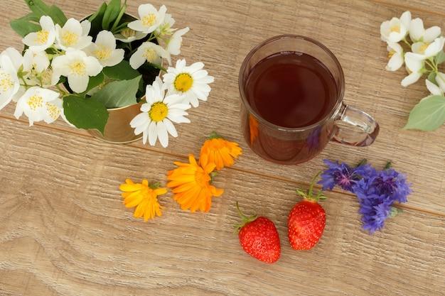 Tazza di tè in vetro con fragole e fiori