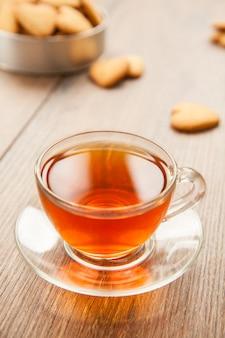 Vetro tazza di tè su un tavolo di legno con una scatola di biscotti.