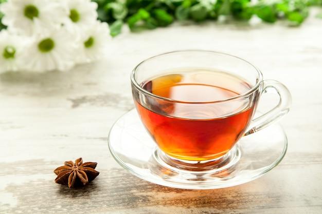 Tazza di tè in vetro su un tavolo di legno con fiori, foglie di menta e anice stellato.