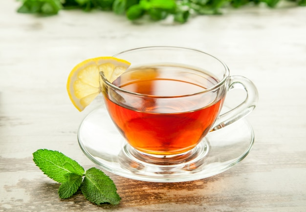 Vetro tazza di tè su un tavolo di legno con foglie di limone e menta.