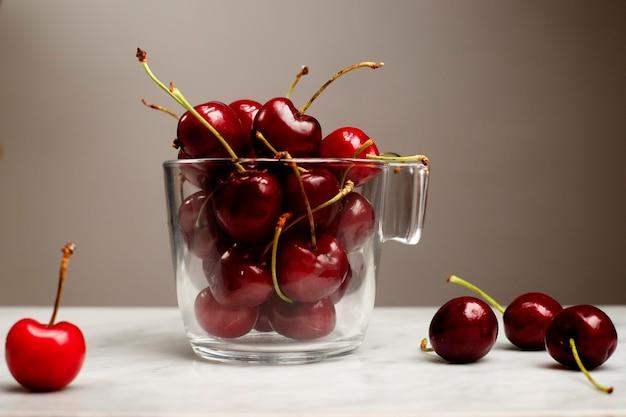 Tazza di vetro con ciliegie su un tavolo di marmo