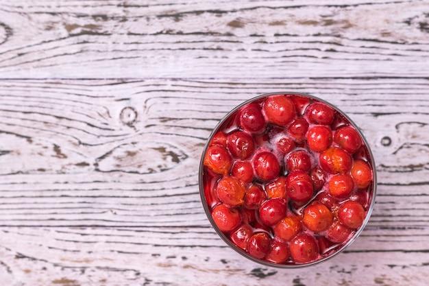 Tazza di vetro con marmellata di ciliegie sulla tavola di legno