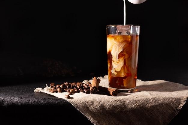 Tazza di vetro con caffè freddo e ghiaccio, chicchi di caffè