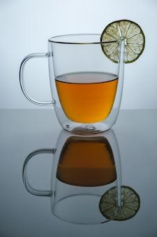 Tazza di vetro con tè caldo e limone sulla superficie dello specchio nero, girato in studio pubblicitario, copia dello spazio