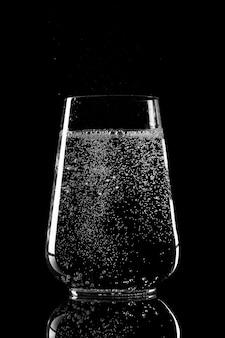 Tazza di vetro con acqua minerale pura su sfondo nero