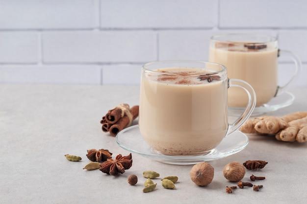 Tazze di vetro di tè masala indiano caldo con spezie invernali sul tavolo