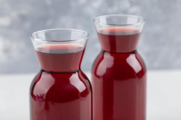 Bicchieri di vetro di vino posti sulla superficie bianca