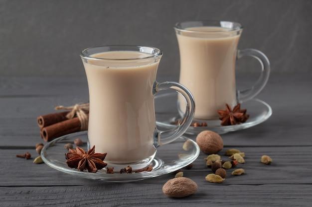 Tazze di vetro con tè masala indiano e spezie sul tavolo di legno grigio