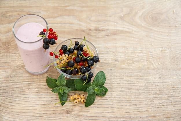 Bicchiere di delizioso yogurt al ribes con bacche fresche di ribes rosso, bianco e nero in una ciotola e foglie di menta su uno sfondo di legno. primo piano messa a fuoco selettiva. vista dall'alto