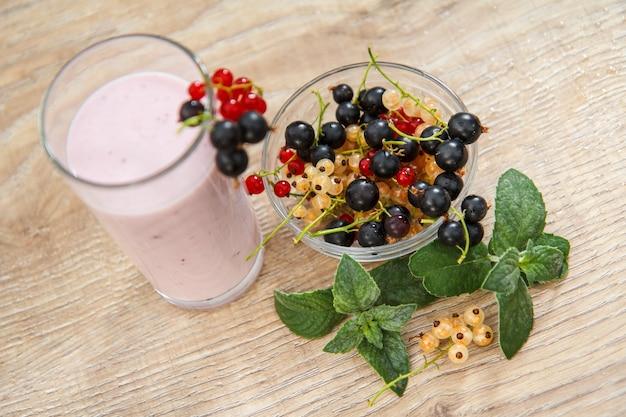 Bicchiere di delizioso yogurt al ribes con bacche fresche di ribes rosso, bianco e nero in una ciotola e foglie di menta su un tavolo di legno. primo piano messa a fuoco selettiva. vista dall'alto