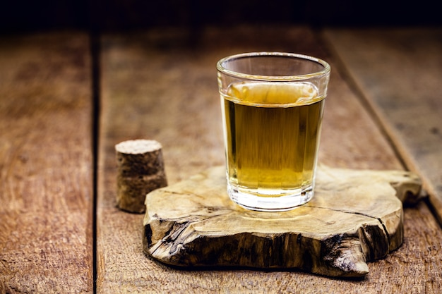 Bicchiere di bevanda alcolica distillata su sfondo di legno con copia spazio per il testo. chiama per rum o cachaça