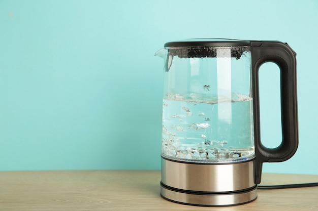 Bollitore elettrico in vetro con acqua bollente su sfondo blu.