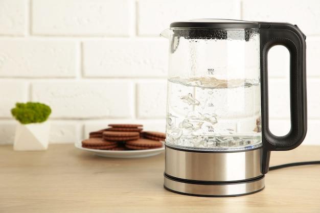 Bollitore elettrico in vetro con acqua bollente e biscotto al cioccolato su sfondo bianco. vista dall'alto.
