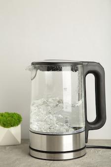Bollitore elettrico in vetro con acqua bollente su sfondo grigio.
