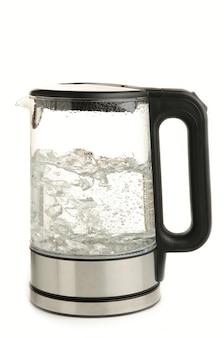 Bollitore elettrico in vetro con acqua bollente, isolato su sfondo bianco.