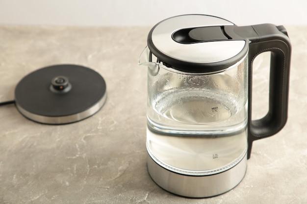 Bollitore elettrico in vetro con acqua su sfondo grigio.