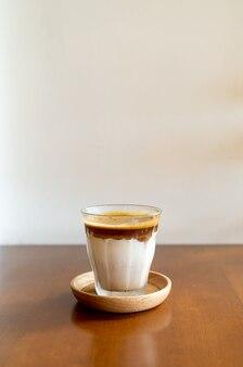 Un bicchiere di caffè espresso mescolato con latte fresco freddo