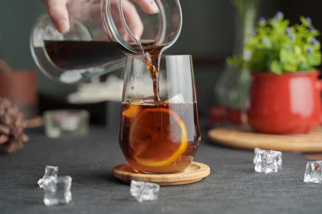 Bicchiere di caffè espresso con succo di limone e limone fresco a fette sulla tavola di legno