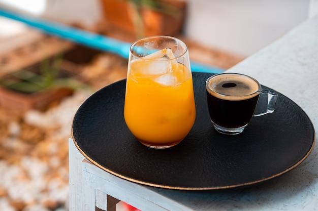 Bicchiere di caffè espresso con succo d'arancia sulla tavola di legno