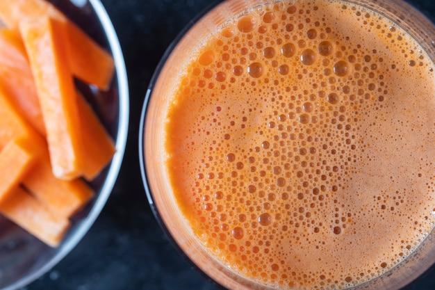 Bicchiere di succo di carota fresco sfondo, vista dall'alto, primo piano. concetto di cibo sano