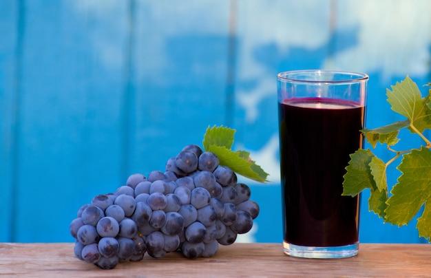 Bicchiere di succo d'uva fresco, un grappolo d'uva alla luce del sole nel cortile