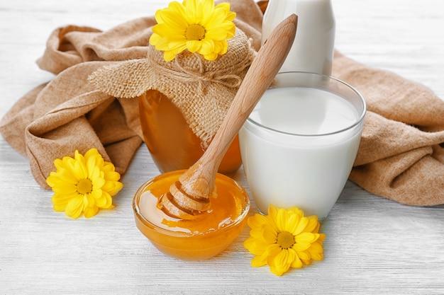 Bicchiere di latte fresco e ciotola con miele dorato sul tavolo di legno bianco