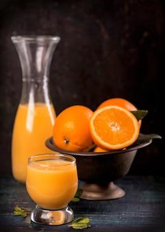 Bicchiere di succo d'arancia fresco con frutta fresca sulla tavola di legno