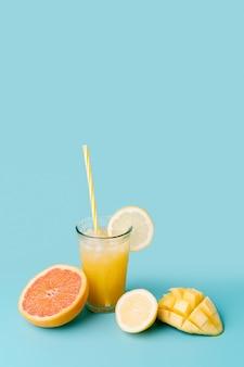 Bicchiere di succo di frutta con cannuccia per un fresco frutto esotico