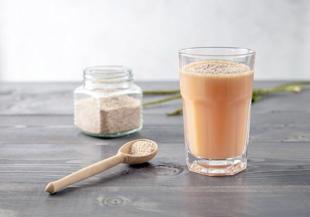 Un bicchiere di frullato di frutta e latte di cocco con la buccia dei semi di piantaggine
