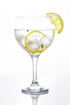 Bicchiere di gin tonic con limone isolato su sfondo bianco