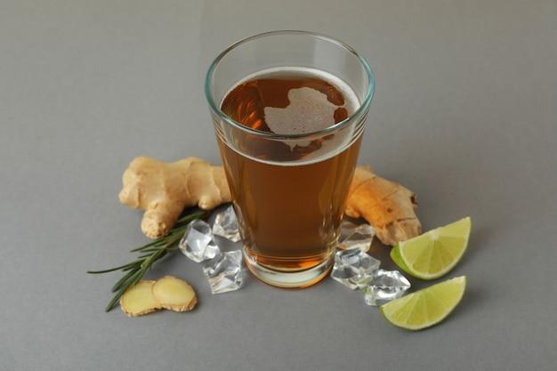 Bicchiere di birra allo zenzero e ingredienti su sfondo grigio