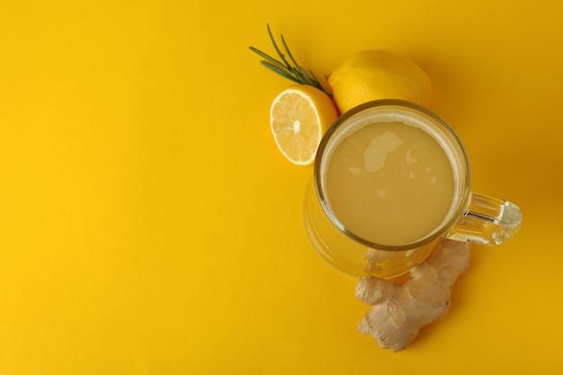 Bicchiere di birra allo zenzero e ingredienti su sfondo giallo