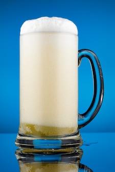 Bicchiere di vetro per birra e tanta schiuma