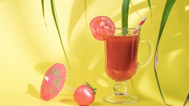 Bicchiere di vetro con succo di pomodoro all'ombra delle foglie su sfondo giallo.
