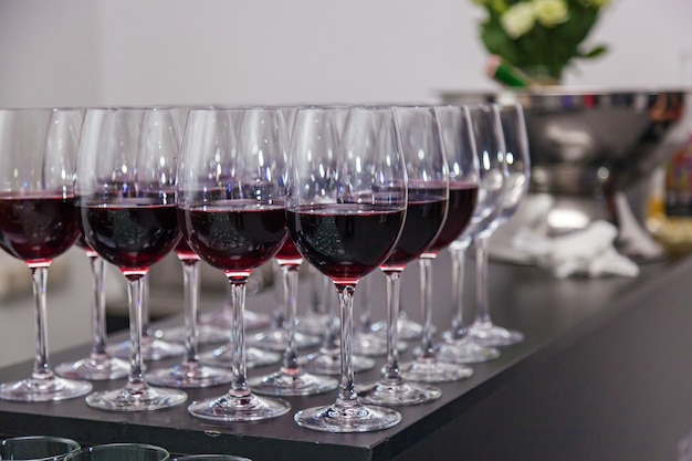 Bicchieri di vetro con vino rosso al bar, profondità di campo ridotta