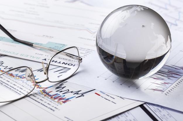 Sfera del globo di vetro in raggi di luce sullo sfondo dei grafici aziendali