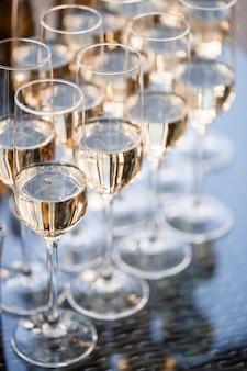 Calici di vetro riempiti di champagne frizzante e appoggiati sul tavolo