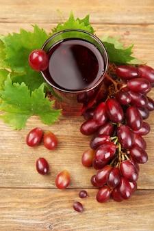 Bicchiere di succo d'uva su fondo in legno