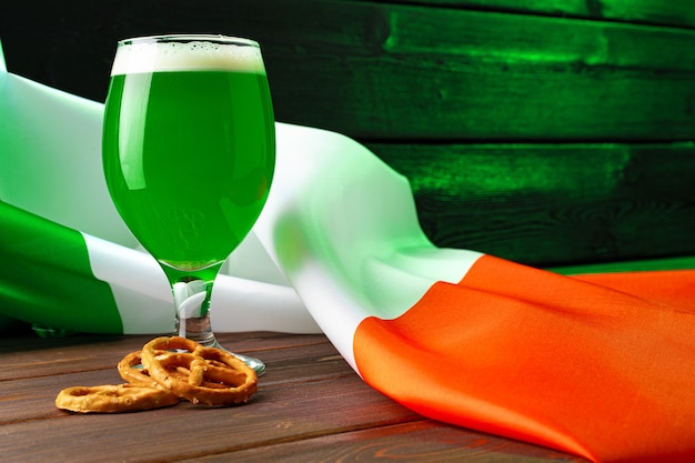 Bicchiere di birra verde contro la bandiera dell'irlanda da vicino