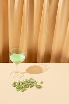 Un bicchiere di bevanda verde e un fagiolo accanto su uno sfondo di tenda beige concetto di cibo per feste