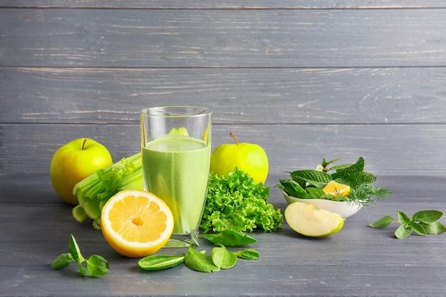 Bicchiere di succo verde sano con frutta e verdura sulla tavola di legno