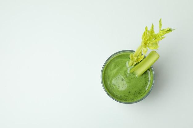 Bicchiere di frullato verde con? elery su sfondo bianco