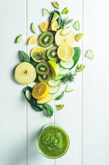 Bicchiere di frullato verde con verdure, frutta ed erbe aromatiche di cui è composto su una superficie di legno bianca piatta
